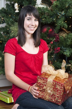 A lovely young teen sitting in front of a Christmas tree holding a present.
