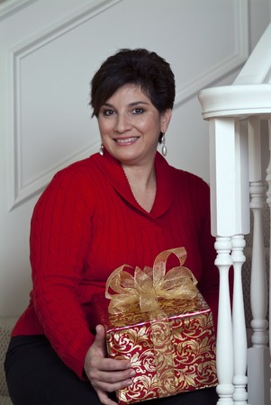 A charming lady sitting on her stairway holding a beautifully wrapped present.