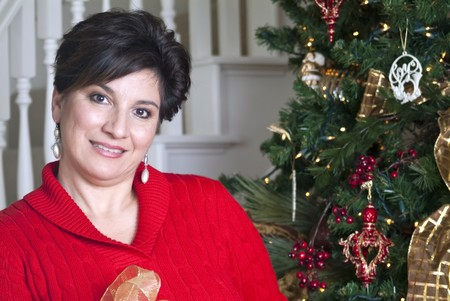 An attractive smiling woman standing by a beautifully decorated Christmas tree.  Archivio Fotografico