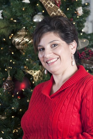 A smiling woman standing in front of a wonderfully decorated Christmas tree.  Archivio Fotografico