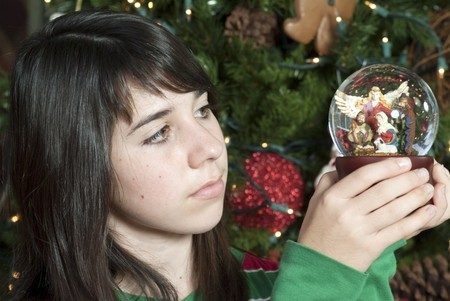 A lovely young girl looks thoughtfully at the nativity scene inside the music globe. Archivio Fotografico