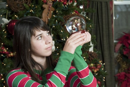 A lovely young girl gazing at a small globe containing a nativity scene.