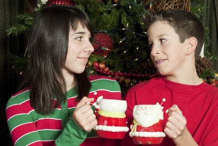 Two children sitting by of a lovely Christmas tree enjoying mugs of hot chocolate. Archivio Fotografico