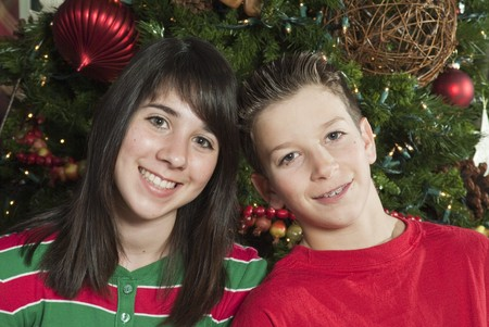 Two youngsters with great smiles sitting in front of a Christmas tree.
