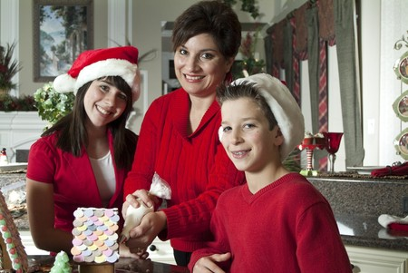 A mother and her two children working together to decorate a gingerbread house. Archivio Fotografico
