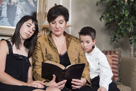 A woman teaches her two children by reading to them from the Bible.