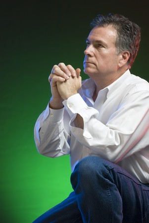 A man kneeling in prayer, with green, blue and red gels applied for creative lighting.