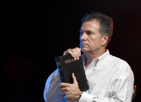 Man contemplating what he has just read in his bible, scene lit with red and blue gels.
