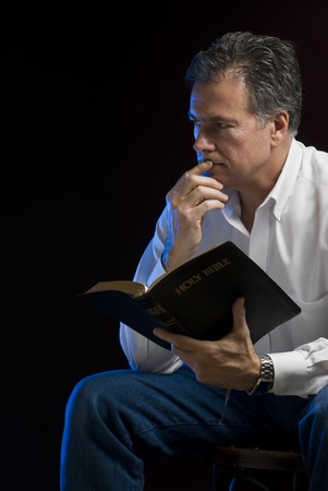 bible study: A man sitting in a dark room contemplating his Bible reading, side lit with blue gel. Stock Photo