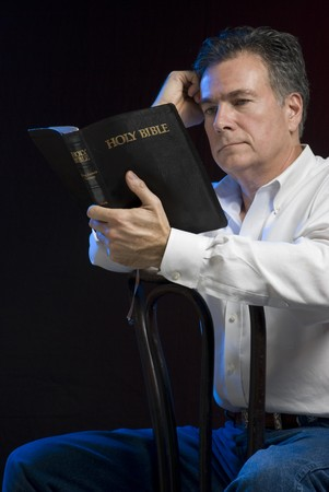 A man sitting in a dark room reading a bible, side lit with blue gel for mood.  Archivio Fotografico