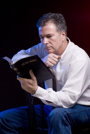 A man sitting astride an old bentwood chair reading a bible, red and blue accent lighting applied.