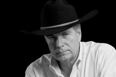 unsmiling: A black and white poitrait of an unsmiling man wearing a cowboy hat.