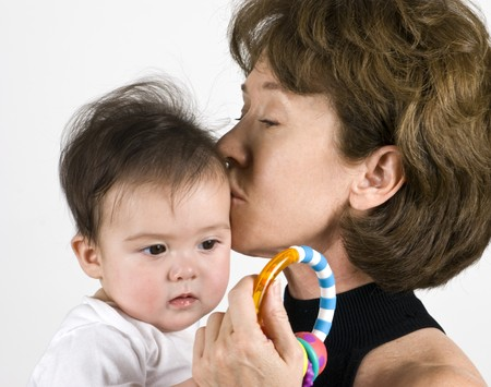 A grandmother loving kisses her baby granddaughter.  Archivio Fotografico