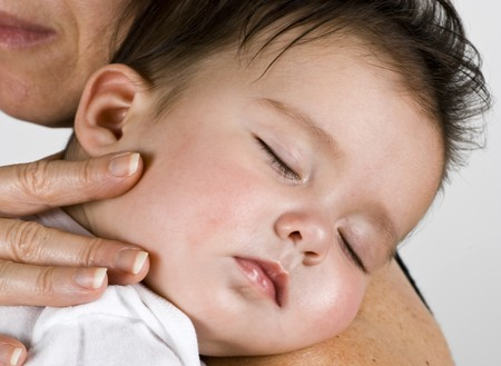A beautiful little baby girl fast asleep on a woman shoulder.