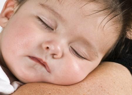 catnap: A beautiful little baby girl fast asleep on a woman shoulder.