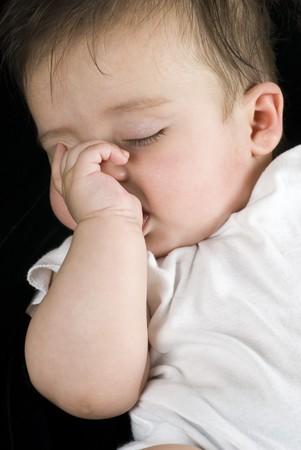 A close up of a beautiful little baby girl sleeping peacefully with her thumb in her mouth.