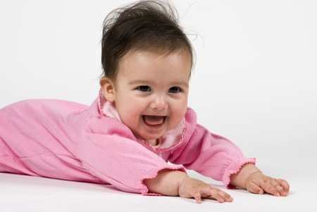 A happy darling little baby girl dressed in pink, stretched out on a white backdrop.  Archivio Fotografico