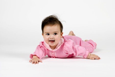 A darling little baby girl smiling happily while lying on a white backdrop.