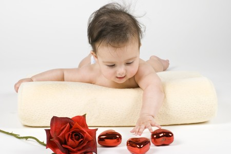 A sweet little baby girl reaching for a rose and some heart shaped ornamets. Archivio Fotografico
