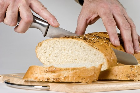 A man with long knife slicing through a large loaf of bread.