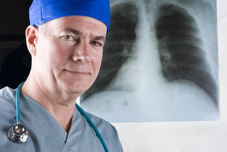 A smiling doctor standing in front of an x-ray film. Standard-Bild
