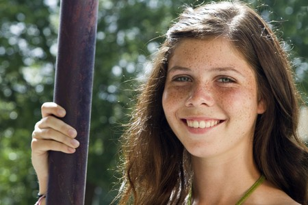 A pretty green eyed, freckled faced teenaged girl smiles a lovely smile for the camera.  Archivio Fotografico