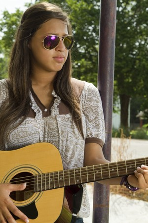 A pretty teen in sunglasses strums on her acoustical guitar.