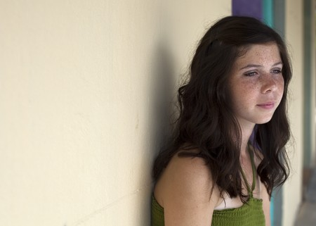 A pretty green eyed teenager who appears sad or pensive leaning against a wall. Archivio Fotografico