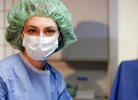 외과 의사 또는 외과 간호사는 큰 파란 질문의 눈을 가진 카메라에 somberly 보인다.
