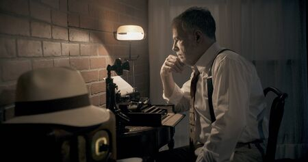 Vintage 1930s era writer sitting at a small desk in a dimly lit room thinking about what he has typed using a portable typewriter.