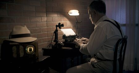 Vintage 1930s era writer sitting at a small desk in a dimly lit hotel room typing on a portable typewriter.