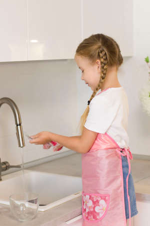 little girl in an apron stands by the kitchen sink.Girl washes dishes
