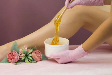 Hair removal in a luxury spa studio. Women's feet wax with saccharin. Hot sugar. The product of the wax bowl. Salon bank. Purple, lilac background
