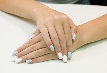 two-tone manicure with blue and white nail Polish Imagens