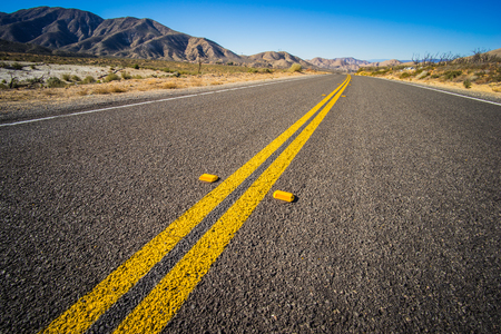run down: Double yellow lines run down the center of a highway in the desert wilderness of Mojave in California.