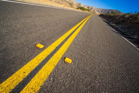 Abandoned stretch of new asphalt road in the Mojave Desert of California. Imagens