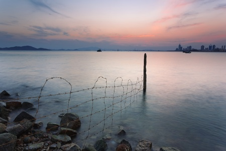 and the stakes: Barbed wire stakes and urban sea view scenery