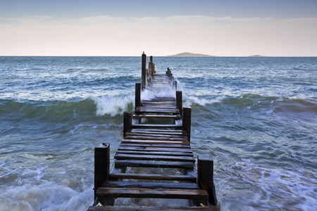 high stakes: Wooden trestle in sea water
