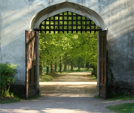 Opened gate of the castle with grill bars up and view to the beautiful garden full of trees Stock Photo