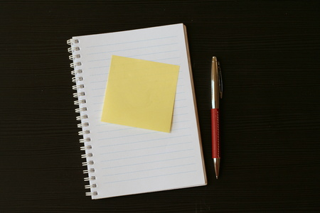 scratchpad: White lined scratchpad (notepad) with yellow postit card and red pen on a black wooden table Stock Photo