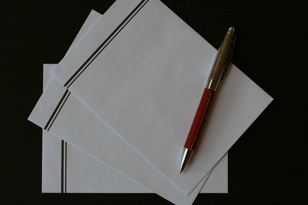 condolence: White envelopes with black stripe with red pen prepared on the black table for sending the condolence letter or funeral card.