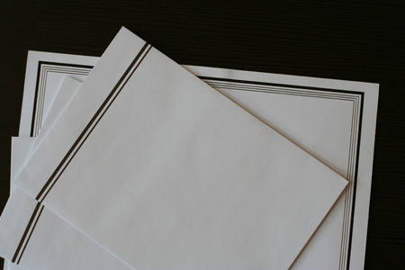 condolence: White funeral notice with black border and envelopes prepared on the table for sending.