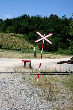 cross ties: Railroad crossing sign in the nature with rusty wagons and sleepers in the background. Blue sky above and dry grass on the ground.