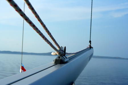 spar: Sailing boom spar on the yacht tied with sailing ropes. Adriatic sea and blue sky over the horizon in the background. Zadar, Croatia.