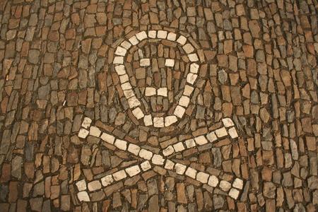 skull with crossed bones: Symbol of crossed bones and skull created from white cobbles on the ground. Taken in Sedlec, Kutna Hora ossuary, Czech Republic Stock Photo