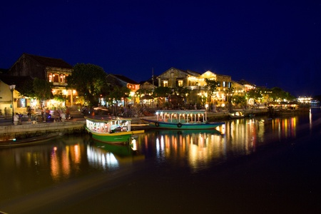 duskiness: Hoi An ancient city full of lights from lanterns and boats on the river Thu Bon. Evening picture with shining lights from lanterns and reflection in the river. Central Vietnam, Asia. Stock Photo