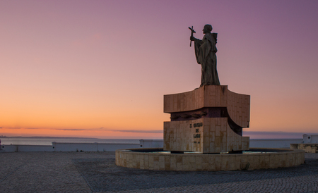 The statue of Saint Goncalo, patron of mariners near Atlantic ocean. Sunrise picture with violet light from sun rising. Saint Goncalo with cross blessing to sailors during oversea discoveries.