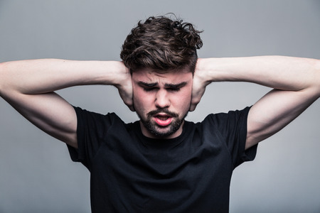hands over ears: Young man in black T-shirt Stock Photo