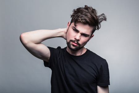 Young man in  black T-shirt doubting