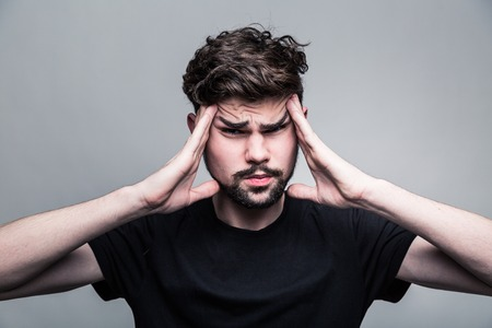 frowning: Young man feeling pain, frowning with hand on head with gray background